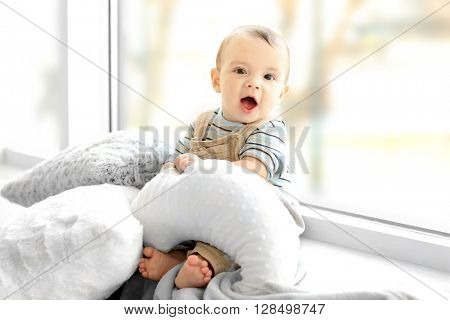 Little baby boy with pillows sitting on windowsill at home