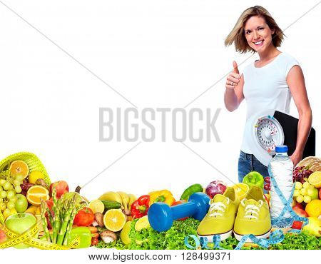 Beautiful fitness girl with scales and vegetables.