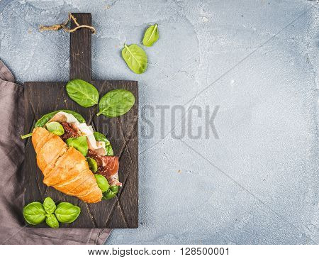Croissant sandwich with smoked meat Prosciutto di Parma, sun dried tomatoes, fresh spinach and basil on dark wooden board over stone textured grey background, top view, copy space