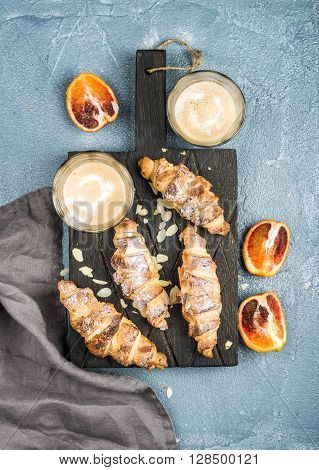 Italian style home breakfast. Latte coffee, almond croissants and red bloody oranges on dark wooden serving  board over concrete textured table, top view