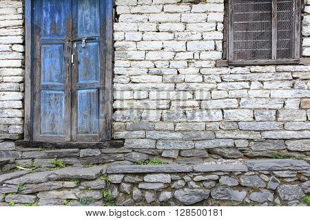 Grunge gray bricks wall with old rough wooden blue door and brown window it is a side view of house.