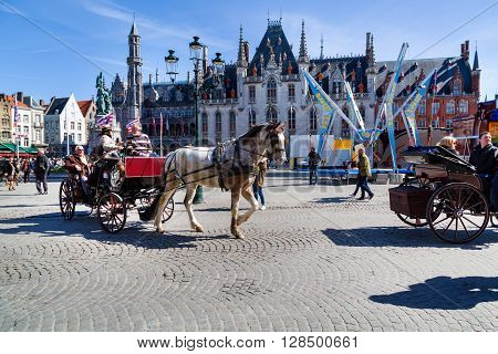 Bruges, Belgium - April 10, 2016:  Fiaker with tourists in Market place or Grote Markt square,  popular belgian destination Brugge, Belgium
