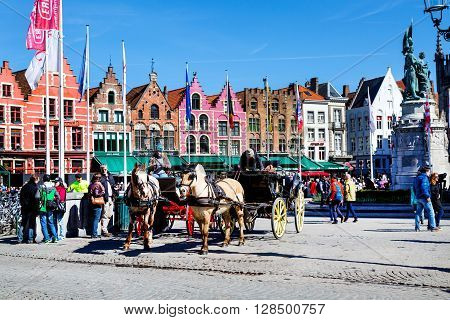 Bruges, Belgium - April 10, 2016: Market place or Grote Markt square with colorful traditional houses, fiaker, people walking in popular belgian destination