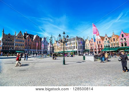 Bruges, Belgium - April 10, 2016: Market place or Grote Markt square with colorful traditional houses, people walking in popular belgian destination