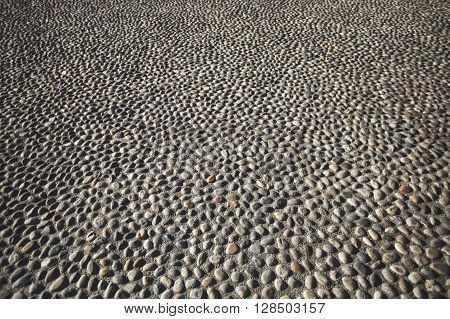 Pavement made of circle accurate stones on the old street in Europe.
