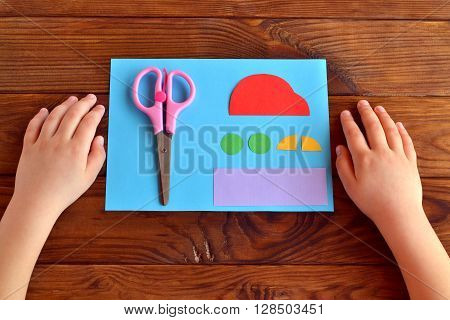 Paper car and parts, scissors. Child put his hands on the wooden table. Kids art. Kids crafts. Child does a greeting card father's day
