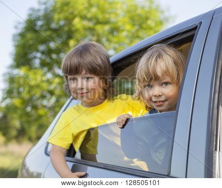 two cheerful child sitting in the car on nature