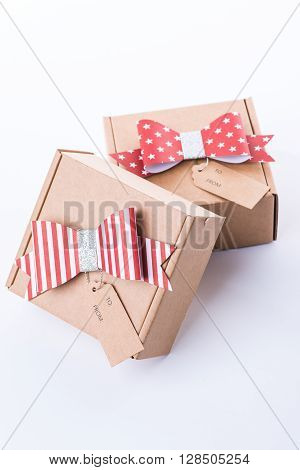 Brown Cardboard Gift Box With A Red Bow And Tag