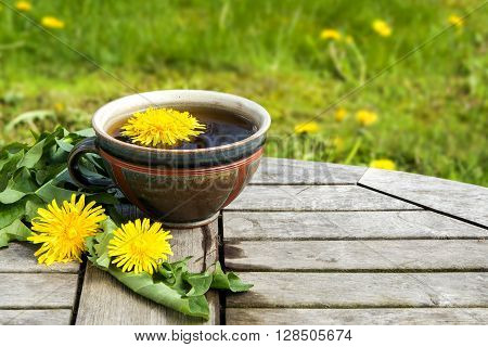 tea from dandelion in a rustic earthenware cup on a wooden table against a blurred dandelion meadow with copy space selected focus narrow depth of field