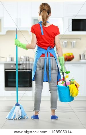 Cleaning concept. Woman with floor mop and bucket with washing fluids, back view