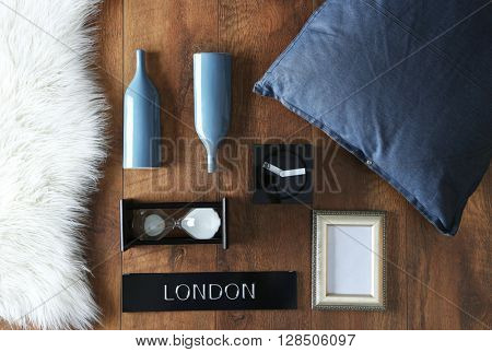 Little details of home interior on brown wooden background, top view