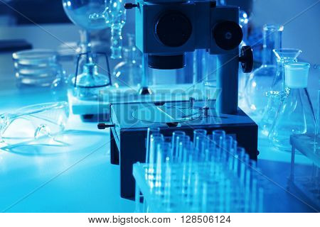 Microscope and different test tubes and flasks in laboratory