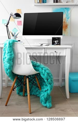 Modern wide screen monitor on white table and chair in room interior