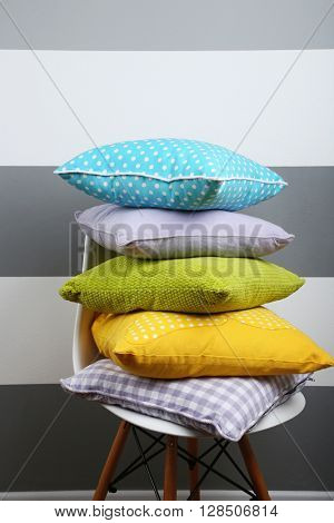 Colorful pillows on chair, on striped grey wall background