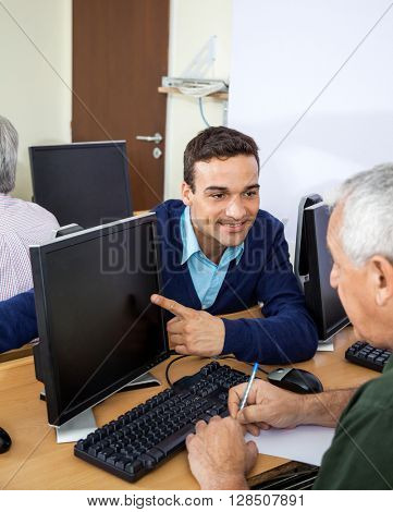 Happy Teacher Showing Something To Senior Student On Computer