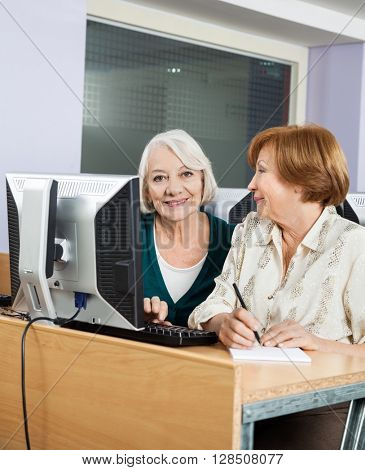 Happy Senior Woman With Classmate Using Computer In Class