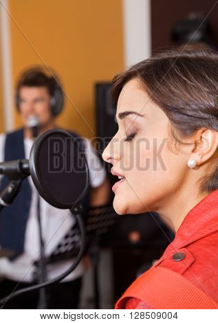 Woman With Eyes Closed Singing In Studio
