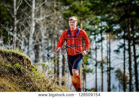Ekaterinburg Russia - April 24 2016: young man skyrunning running with walking sticks in hands during a Mountain marathon