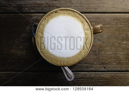 cup of fresh cappuccino on the brown oak table