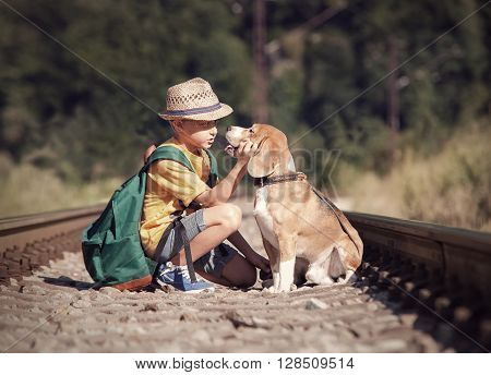 Little boy with his dog sitting on the railway