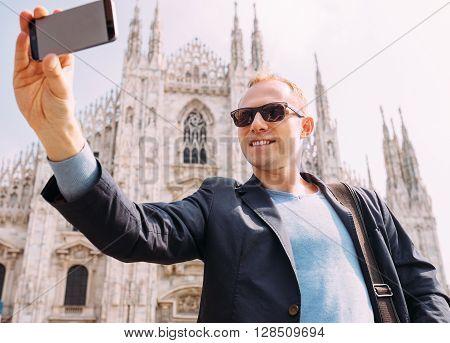 Man take a selfie photo on Duomo di Milano background