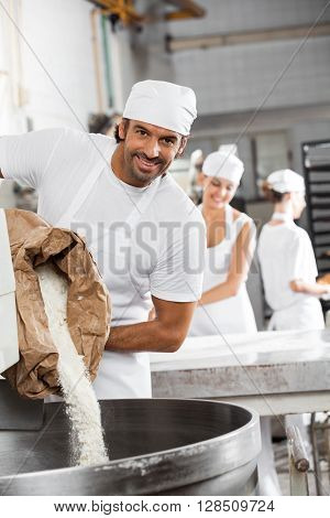 Happy Male Baker Pouring Flour In Kneading Machine