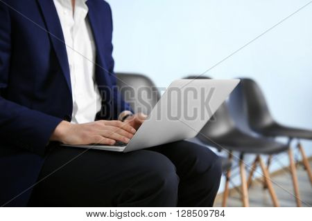 Young man in suit sitting on chair with laptop closeup