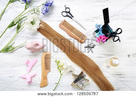 Strand of hair with flowers and barber tools on light wooden background