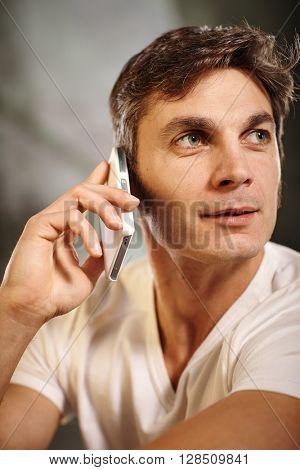 Man talking on mobilephone, looking away.