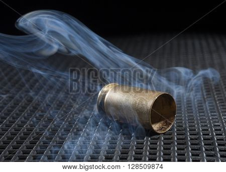 Empty brass from a handgun on a black grate with smoke