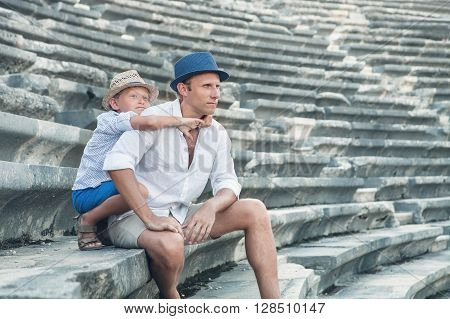 Father with son sitting on antique amfitheater steps. Side Turkey