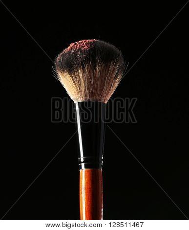 Make up brush with powder on black background
