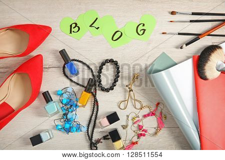 The word BLOG with female fashion accessories on wooden table, top view