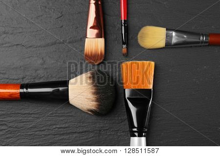 Professional makeup brushes on black texture, top view