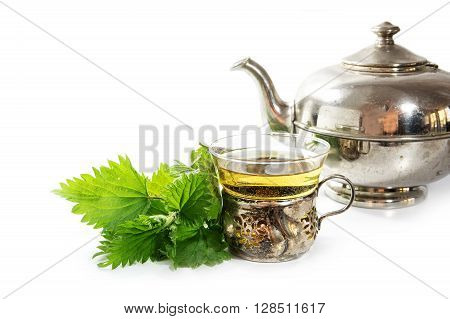 silver teapot and vintage cup with nettle tea and some fresh leaves on a white background healing herb directly from nature selected focus narrow depth of field