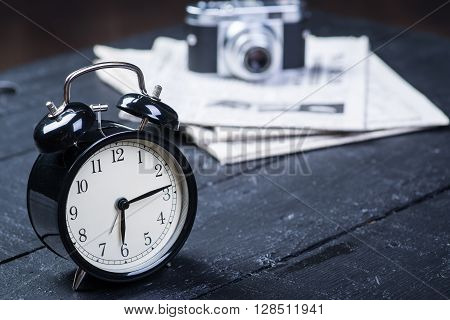 Black alarm clock with camera and newspaper on a wooden table