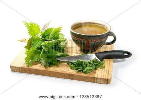 Preparing nettle tea fresh leaves knife and a rustic teacup on a wooden cutting board isolated with shadows on a white background selected focus narrow depth of field