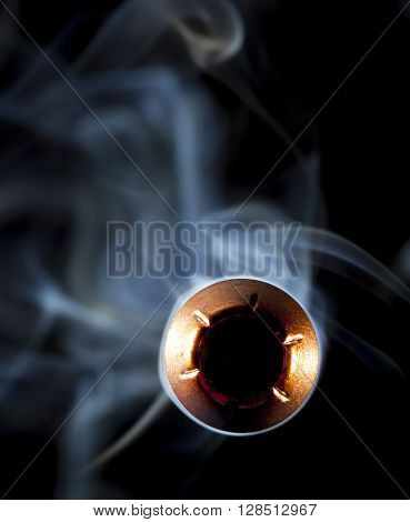 Bullet with a hollow point and smoke behind pointed at the camera