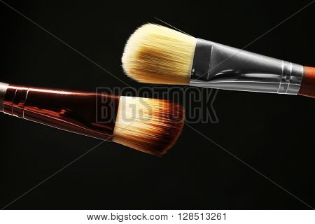Professional makeup brushes on black background