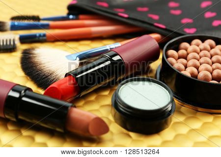 Makeup set with beautician, brushes and cosmetics on yellow background
