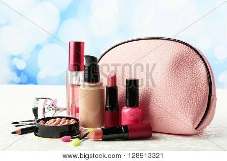 Makeup set with beautician, eyelash curler, brushes and cosmetics on light background