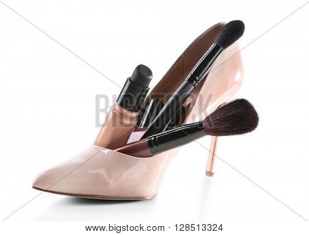 Makeup set with beige woman's shoe, brushes and cosmetics, isolated on white
