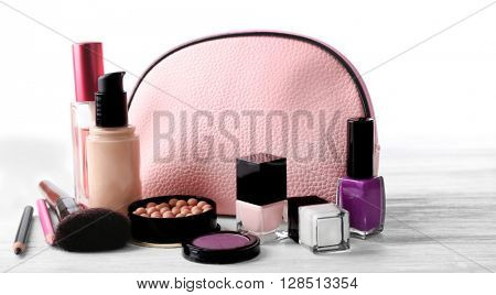 Makeup set with beautician, brush and cosmetics on light background