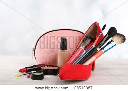 Makeup set with beautician, red woman's shoe, brushes and cosmetics on light background