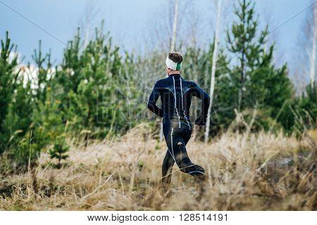 young male marathon runner running down hill amongst dry grass
