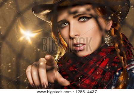 Fantasy portrait of a beautiful girl in a cowboy style looking through Dreamcatcher