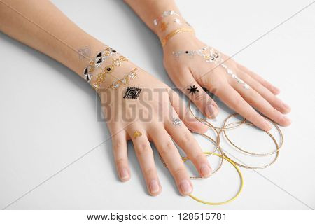 Female hands with flash tattoo holding bracelets on white background