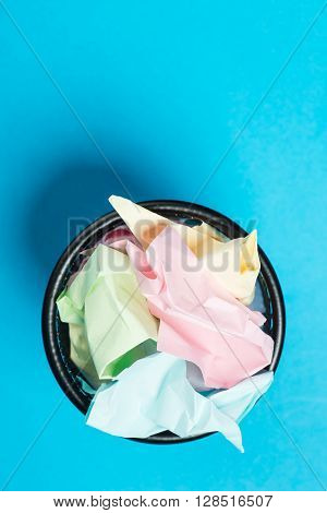 Colorful Crumpled Paper In A Black Garbage Bin Over The Blue Background