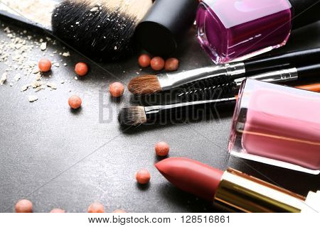 Decorative cosmetics and accessories for makeup on grey background