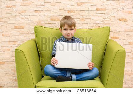 Little boy with laptop in armchair against brick wall background